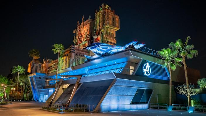 A large metallic structure lighted in blue with the Avengers logo in front of the Guardians of the Galaxy tower