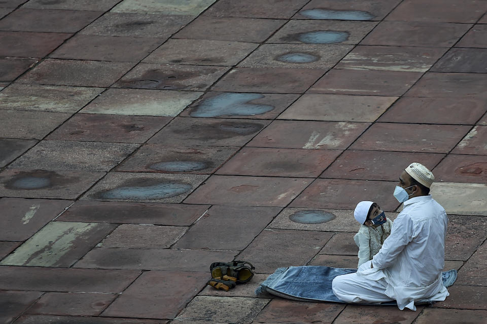 A Muslim father and his son wait to offer a special morning prayer to kick off the Eid al-Adha, the feast of sacrifice, at Jama Masjid mosque in New Delhi on August 1, 2020. (Photo by Money SHARMA / AFP) (Photo by MONEY SHARMA/AFP via Getty Images)