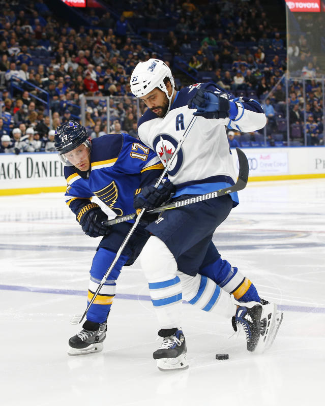 St. Louis Blues' Jaden Schwartz, left, and Winnipeg Jets' Dustin Byfuglien battle for the puck during the second period of an NHL hockey game Friday, Feb. 23, 2018, in St. Louis. (AP Photo/Billy Hurst)