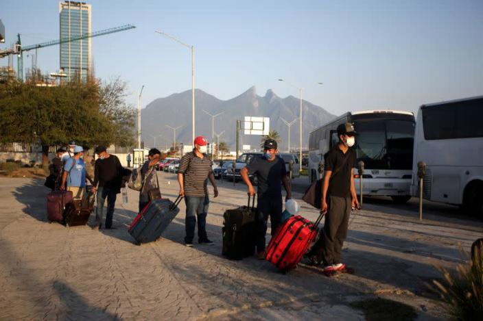 Migrants seeking for a U.S. work visa are pictured as they waiting to take a bus that will take to their hotel in Monterrey