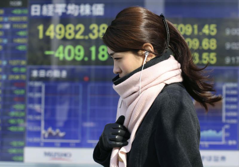 A woman walks by an electronic stock board of a securities firm in Tokyo, Monday, Jan. 27, 2014. Asian stock markets tumbled Monday as investors factored in the possibility of slowing growth in China and a further reduction in U.S. central bank stimulus. Japan's Nikkei 225 sank 2.6 percent to 14,993.89 as investors sought out havens such as the Japanese yen, causing it to rise against the dollar which is negative for export stocks. (AP Photo/Koji Sasahara)
