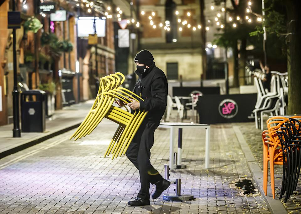 Bar staff clearing away tables for the evening in Manchester. The Government is expected to announce new measures later today that could see pubs and bars forced to close to combat the spread of the virus in northern England and other areas suffering a surge in Covid-19 cases. (Photo by Danny Lawson/PA Images via Getty Images)
