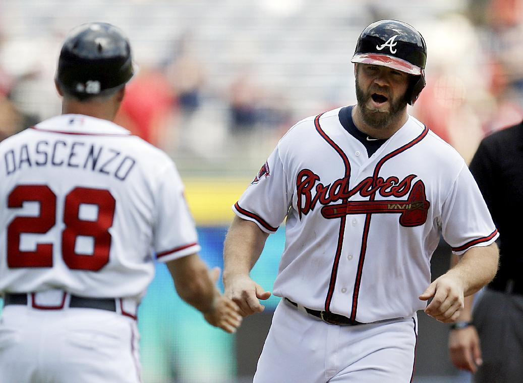 Atlanta Braves' Evan Gattis, right, is greeted by third base coach Doug Dascenzo after hitting a two-run home run to score teammate Freddie Freeman in the first inning of a baseball game against the Philadelphia Phillies, Wednesday, June 18, 2014, in Atlanta. (AP Photo/David Goldman)