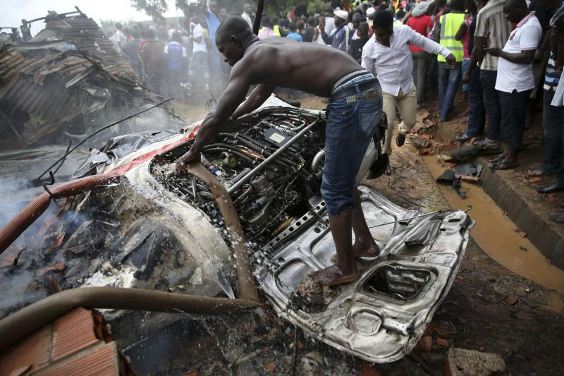 A man tries to extinguish a fire from the engine of a plane at the site of a plane crash near the Lagos international airport