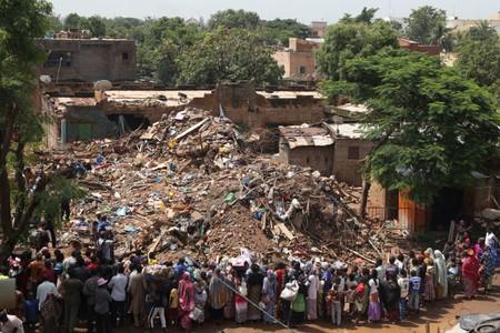 People look at the site of a collapsed building in Bamako