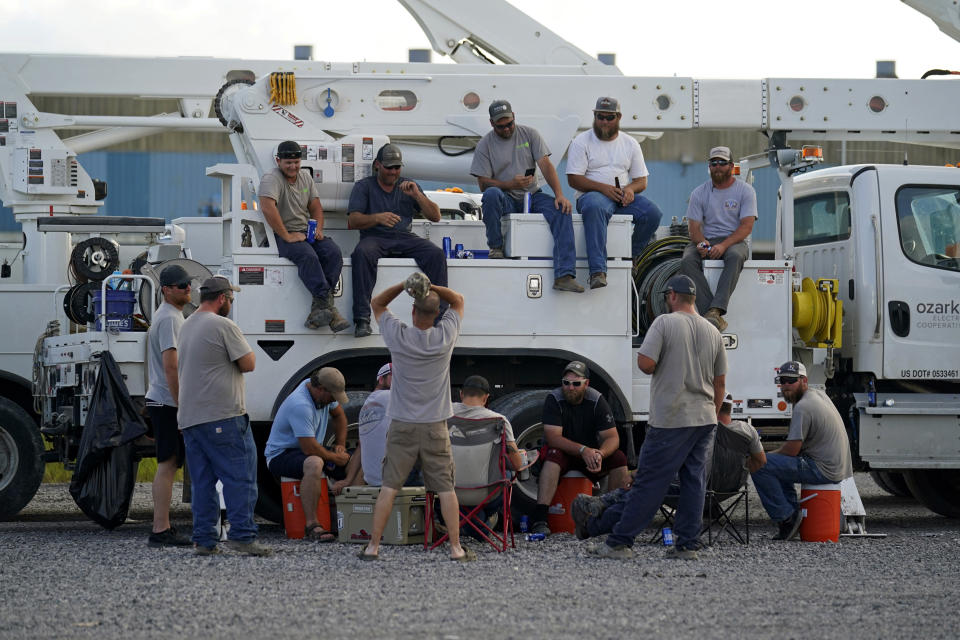 Electrical workers congregate in the evening after parking their trucks after a day's work at a tent city in Amelia, La., Thursday, Sept. 16, 2021. In the wake of hurricanes, one of the most common and comforting sites is the thousands of electric workers who flow into a battered region when the winds die down to restore power and a sense of normalcy. (AP Photo/Gerald Herbert)