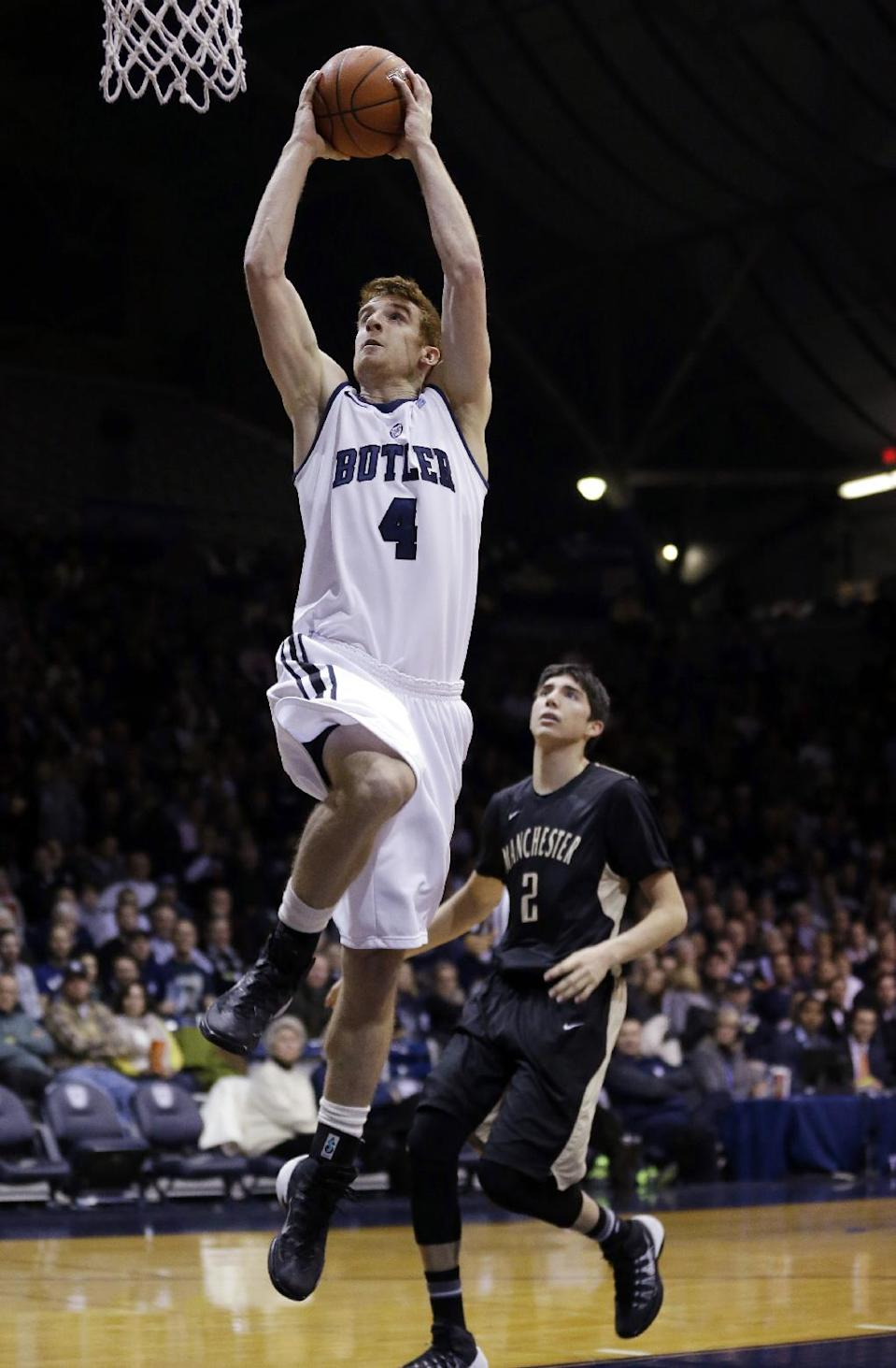 Manchester guard Chase Casteel (4) gets a bucket in front of Manchester guard Blake Brouwer in the first half of an NCAA college basketball game in Indianapolis, Monday, Dec. 9, 2013. (AP Photo/Michael Conroy)