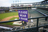 A COVID-19 sign urging fans to wear their masks is threaded through a drink holder in the upper deck of Coors Field before the Colorado Rockies host the Cincinnati Reds in a baseball game, Thursday, May 13, 2021, in Denver. (AP Photo/David Zalubowski)
