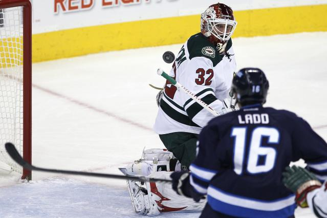 Minnesota Wild's goaltender Niklas Backstrom (32) and Winnipeg Jets' Andrew Ladd (16) keep their eyes on the rebound during the first period of an NHL game in Winnipeg, Manitoba, Saturday, Nov. 23, 2013. (AP Photo/The Canadian Press, John Woods)