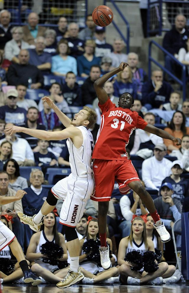 Connecticut's Niels Giffey (5) fights for a rebound with Boston University's Malik Thomas (31) during the first half of an NCAA college basketball game in Storrs, Conn., on Sunday, Nov. 17, 2013. (AP Photo/Fred Beckham)