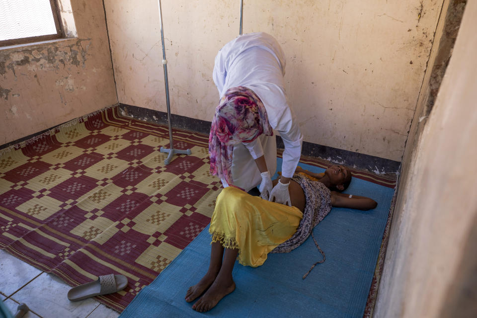 A Sudanese midwife checks a malnourished pregnant refugee woman from Ethiopia's Tigray region, inside the Mercy Corps clinic at Umm Rakouba refugee camp in Qadarif, eastern Sudan, Monday, Dec. 7, 2020. (AP Photo/Nariman El-Mofty)