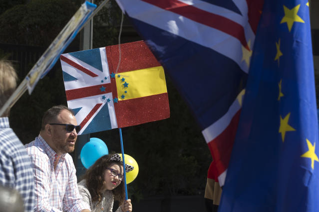 A young girl sits with a split British and Spanish flag during an anti Brexit protest in the Plaza Margaret Thatcher in Madrid, Spain, Saturday, March 23, 2019. Coinciding with the anti Brexit march in London, the Eurocitizens campaign group have organized a protest in the Spanish capital calling for the protection of British citizens living in Spain while asking for a second Brexit referendum. (AP Photo/Paul White)
