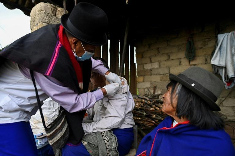 An indigenous nurse from the Misak ethnic group inoculates an elderly man with a Sinovac vaccine in Colombia's Cauca department in April 2021