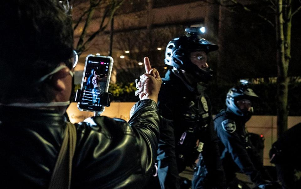 A person records police officers at a protest over the death of Daunte Wright