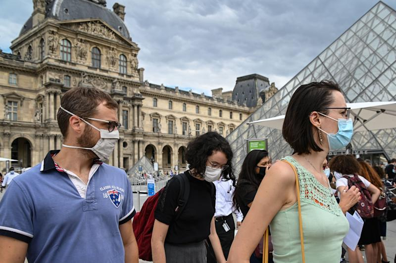 Tourists wearing protective face masks walk past the Louvre Pyramid (Pyramide du Louvre) designed by Ieoh Ming Pei, at the Cour Napoleon, in Paris, on August 15, 2020. (Photo by BERTRAND GUAY / AFP) / RESTRICTED TO EDITORIAL USE - MANDATORY MENTION OF THE ARTIST UPON PUBLICATION - TO ILLUSTRATE THE EVENT AS SPECIFIED IN THE CAPTION (Photo by BERTRAND GUAY/AFP via Getty Images)