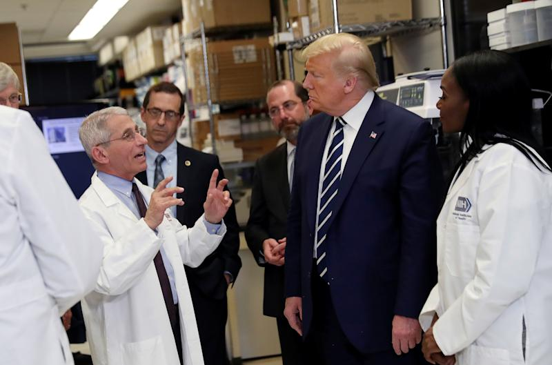 President Donald Trump is flanked by Health and Human Services (HHS) Secretary Alex Azar and National Institutes of Health Doctor Kizzmekia Corbett, research fellow at the NIH Vaccine Research Center, as he listens to Director of National Institute of Allergy and Infectious Diseases Anthony Fauci following a briefing at the Vaccine Research Center in Bethesda, Maryland on March 3, 2020. (Leah Millis/Reuters)