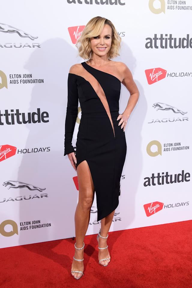 <p>Amanda held nothing back, choosing a revealing asymmetric black dress by Julien Macdonald.<br /><i>[Photo: Getty]</i> </p>