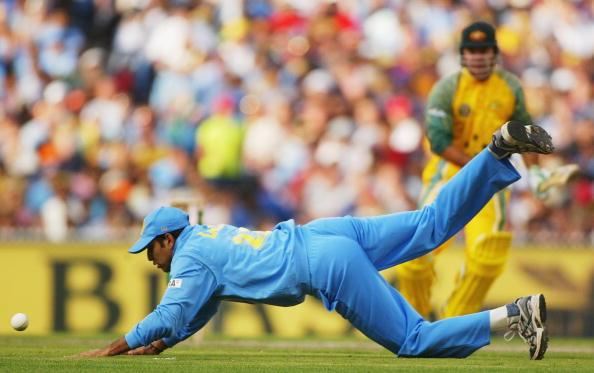 MELBOURNE, AUSTRALIA - FEBRUARY 6:  VVS Laxman of India dives to field with Ricky Ponting of Australia looking on during the first final of the VB Series between Australia and India played at the MCG on February 6, 2004 in Melbourne, Australia. (Photo by Hamish Blair/Getty Images)