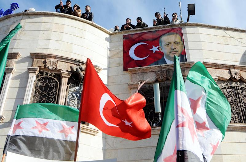 "Turkey-backed Free Syrian Army, FSA, fighters stand on the roof of a building with a poster of Turkey's President Recep Tayyip Erdogan hanging on it in the Syrian town of Azez near the border with Turkey, Friday, Jan. 19, 2018. Turkey's Defense Minister Nurettin Canikli said on Friday in Ankara that his country is determined to carry out a military offensive against an enclave in northwest Syria, saying Syrian Kurdish fighters there pose a ""real"" and ever increasing threat to Turkey. (DHA-Depo Photos via AP)"