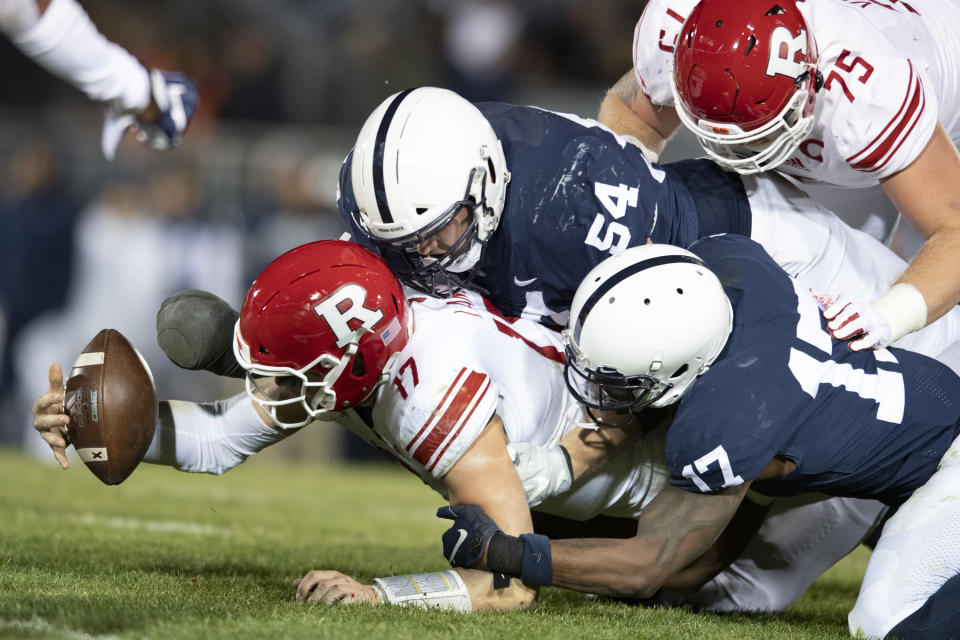 FILE - In this Nov. 30, 2019, file photo, Penn State defenders Robert Windsor (54) and Jayson Oweh (28) cause Rutgers quarterback Johnny Langan (17) to fumble in the third quarter of an NCAA college football game in State College, Pa. Big Ten is going to give fall football a shot after all. Less than five weeks after pushing football and other fall sports to spring in the name of player safety during the pandemic, the conference changed course Wednesday, Sept. 16, 2020, and said it plans to begin its season the weekend of Oct. 23-24. (AP Photo/Barry Reeger, File)