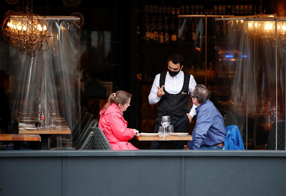 A waiter wearing a face mask serves customers in a restaurant, following the outbreak of the coronavirus disease (COVID-19), in St. Albans, Britain, October 8, 2020.  REUTERS/Peter Cziborra