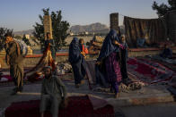 Afghan women walk through a second-hand market where many families sold their belongings before leaving the country or due to financial struggle, in Kabul, Afghanistan. Wednesday, Sept. 15, 2021. (AP Photo/Bernat Armangue)