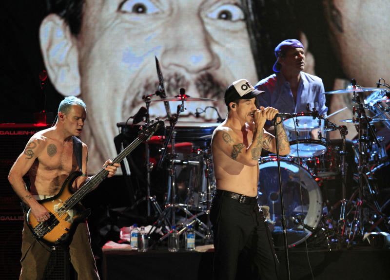 """Red Hot Chili Peppers' Mike """"Flea"""" Balazary, left, singer Anthony Kiedis and drummer Chad Smith, right, perform after induction into the Rock and Roll Hall of Fame Sunday, April 15, 2012, in Cleveland. (AP Photo/Tony Dejak)"""