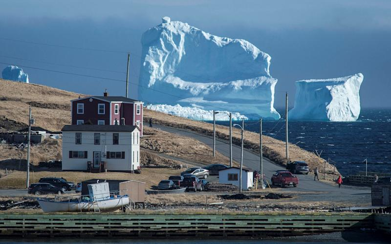 Residents view the first iceberg of the season as it passes the South Shore, also known as