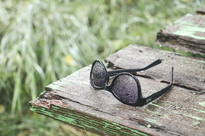 Sunglasses in the rain on old wooden back