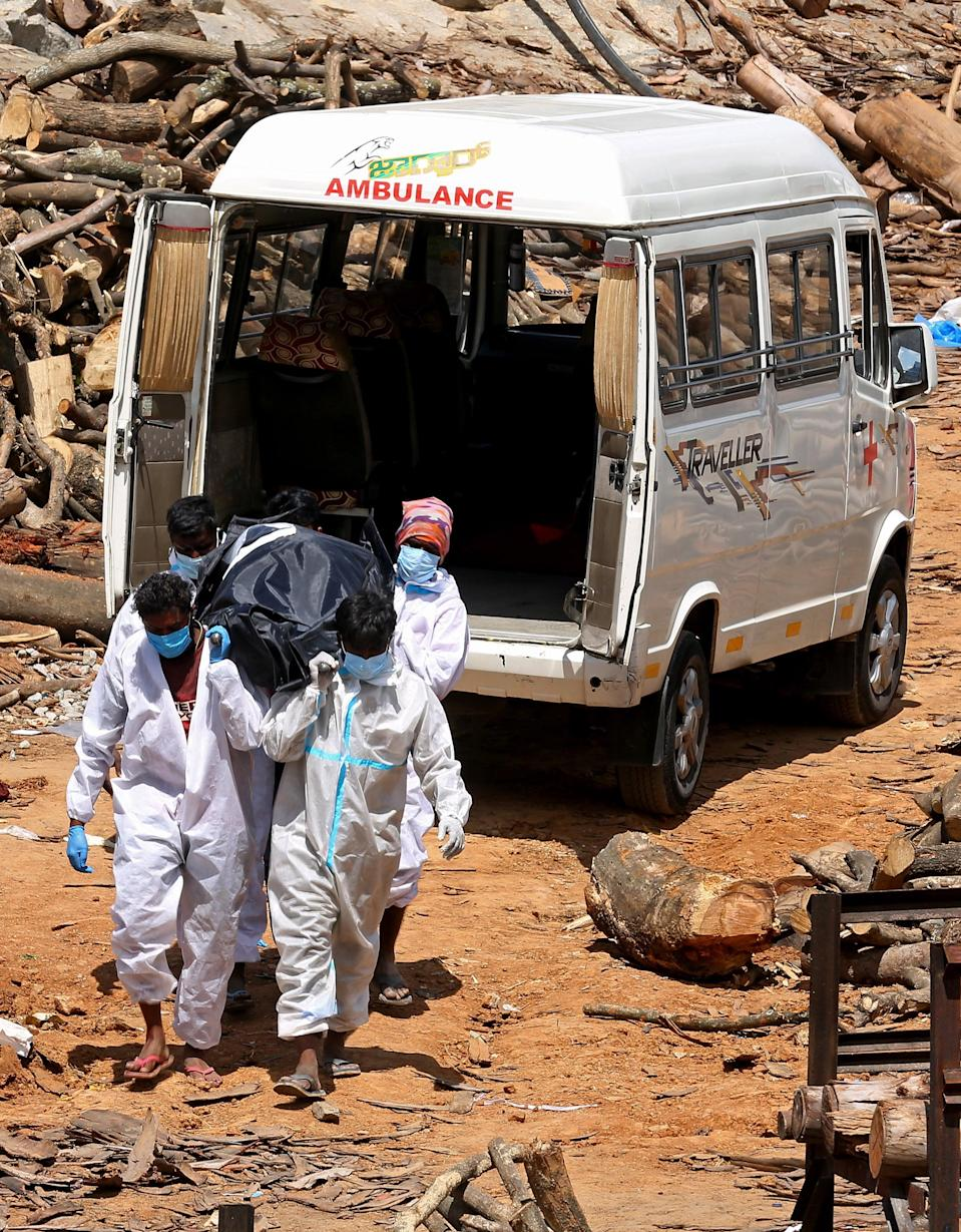 <p>Cremation workers carry the body of Covid-19 victim for the funeral during mass cremation ground</p> (EPA)