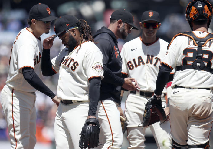 San Francisco Giants starting pitcher Johnny Cueto, second from left, is removed by manager Gabe Kapler, center, in the fourth inning of a baseball game against the Chicago Cubs, Sunday, June 6, 2021, in San Francisco. (AP Photo/Scot Tucker)