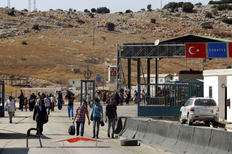 FILE PHOTO: Syrians carry their belongings as they cross back into Syria at the Syrian-Turkish border crossing of Bab al-Hawa in Idlib province
