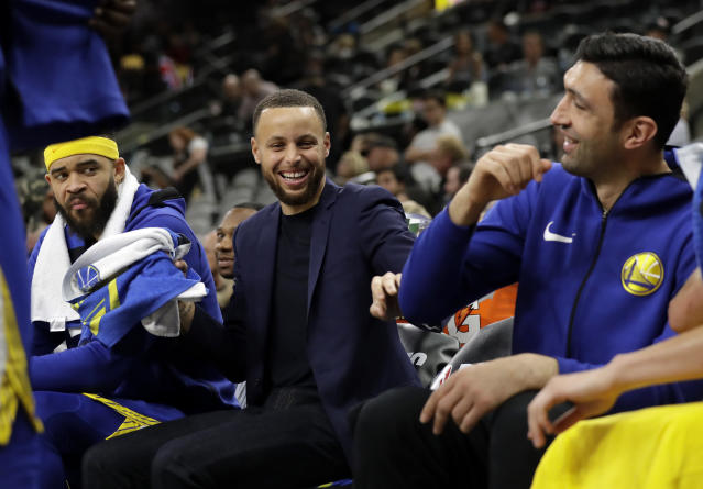 Golden State Warriors' JaVale McGee watches as Stephen Curry, center, jokes with Zaza Pachulia, right, during the second half of Game 3 of the team's first-round NBA basketball playoff series against the San Antonio Spurs in San Antonio, Thursday, April 19, 2018. Golden State won 110-97. (AP Photo/Eric Gay)