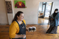 Cafe owner Maria Iatrou, left, serves take-away coffee to customers in Melbourne, Monday, July 6, 2020. As Australia is emerging from pandemic restrictions, the Victoria state capital Melbourne is buckling down with more extreme and divisive measures that are causing anger and igniting arguments over who is to blame as the disease spreads again at an alarming rate. (AP Photo/Andy Brownbill)
