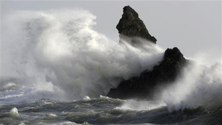 Waves crash over Church Rock in strong winds at Broad Haven, in Wales