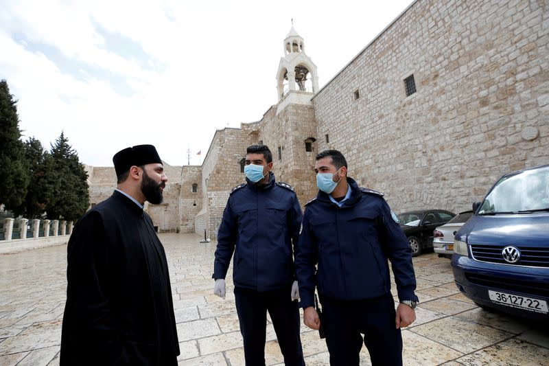 FILE PHOTO: Palestinian police officers stand guard outside the Church of the Nativity that was closed as a preventive measure against the coronavirus in Bethlehem in the Israeli-occupied West Bank