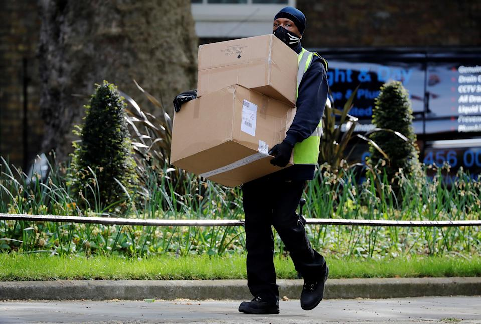 A Hermes delivery courier carries boxes as he makes a delivery to 10 Downing Street, the official residence of Britain's Prime Minister, in central London on May 5, 2020. - Britain's Prime Minister Boris Johnson's fiancee, Carrie Symonds, announced on May 2 that they had named their newborn son after their grandfathers and the hospital doctors who treated the British prime minister for COVID-19. The couple are the first unmarried couple to officially live together in Downing Street and the baby is the third to be born to a serving British prime minister in recent history. (Photo by Tolga AKMEN / AFP) (Photo by TOLGA AKMEN/AFP via Getty Images)