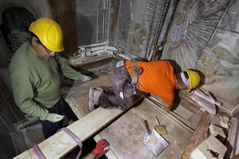 Greek preservation experts place back the marble slab stone that covered the Tomb of Jesus, where his body is believed to have been laid, after it was removed for 3 days to allow the team to do restoration works (AFP Photo/Gali Tibbon)
