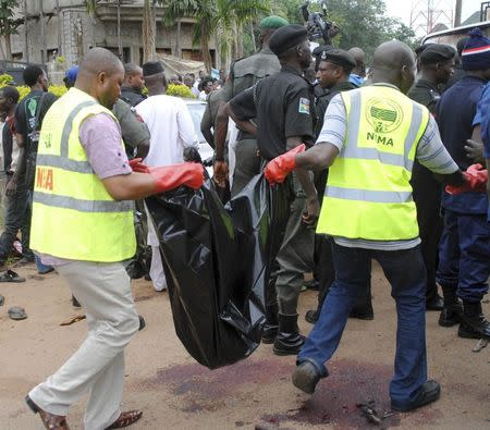 National Emergency Management Agency (NEMA) staff carry a body bag at the scene of a bombing at Alkali Road in Kaduna July 23, 2014. REUTERS/Stringer