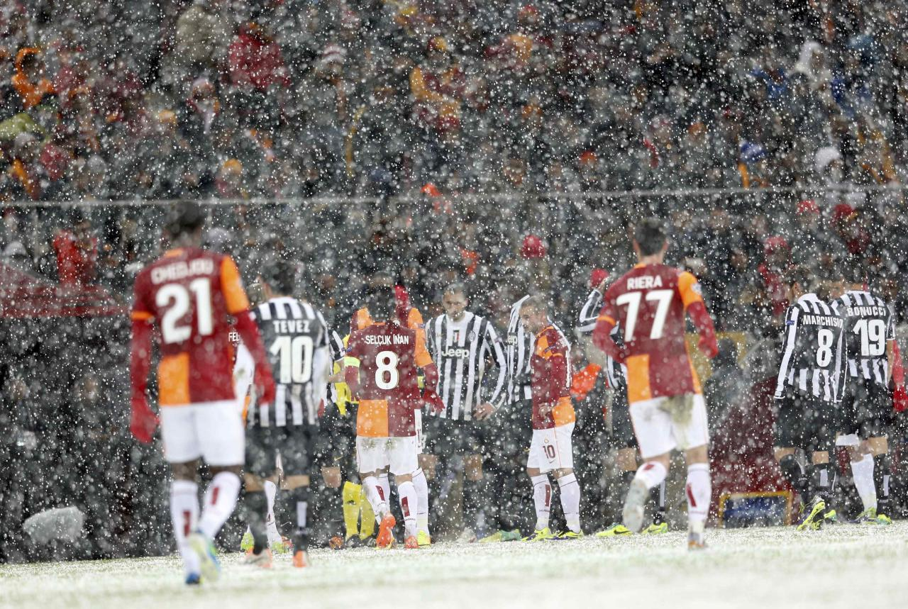 Players of Galatasaray and Juventus walk out of the pitch as their match is paused for 20 minutes due a heavy snowfall during their Champions League soccer match in Istanbul December 10, 2013. REUTERS/Murad Sezer (TURKEY - Tags: SPORT SOCCER)