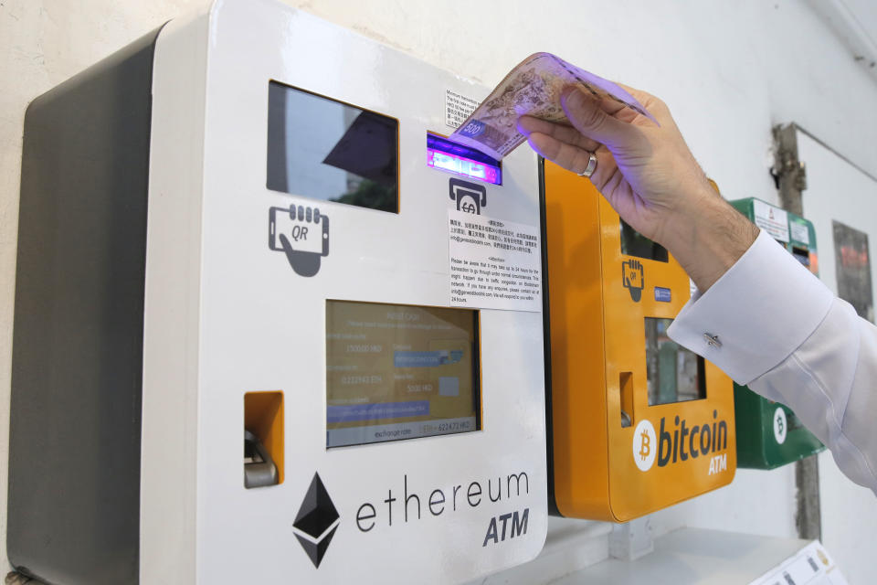 A man uses the Ethereum ATM in Hong Kong, Friday, May 11, 2018. Ethereum is one of the world's popular virtual currencies. (AP Photo/Kin Cheung)