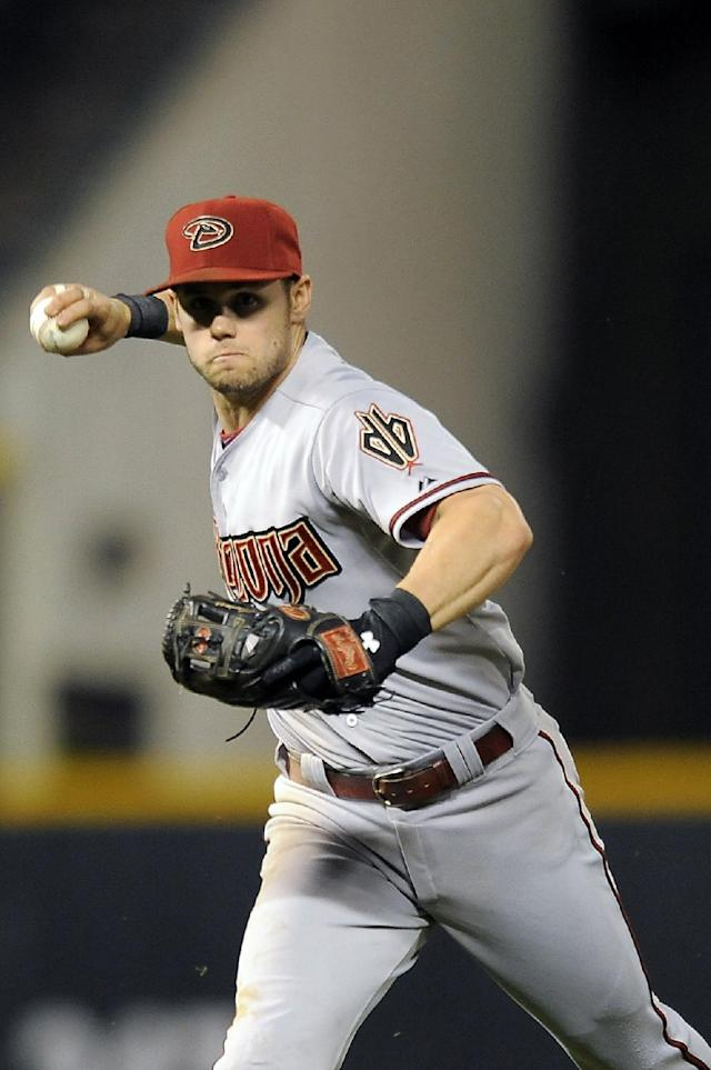 Arizona Diamondbacks shortstop Chris Owings throws out Colorado Rockies Corey Dickerson at first base in the sixth inning of a baseball game on Thursday, June 5, 2014, in Denver. (AP Photo/Chris Schneider)