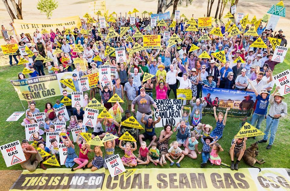 Shot from above, a large crowd holding yellow signs opposing coal seam gas.