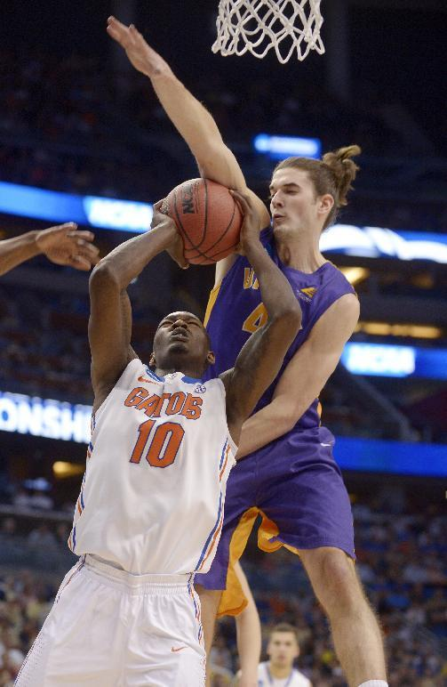 Albany center John Puk, right, blocks a shot to the basket by Florida forward Dorian Finney-Smith (10) during the first half in a second-round game in the NCAA college basketball tournament Thursday, March 20, 2014, in Orlando, Fla. (AP Photo/Phelan M. Ebenhack)