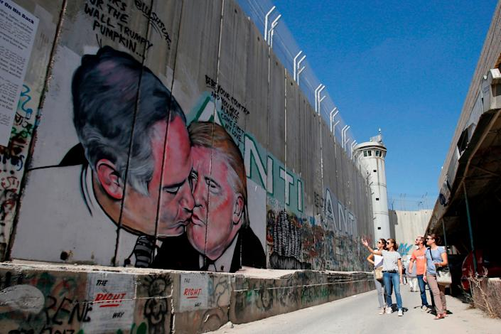 Tourists walk past a graffiti by street artist Lushsux, depicting US President Donald Trump kissing Israeli Prime Minister Benjamin Netanyahu drawn on the controversial Israeli separation barrier separating the West Bank town of Bethlehem from Jerusalem, on October 29, 2017.