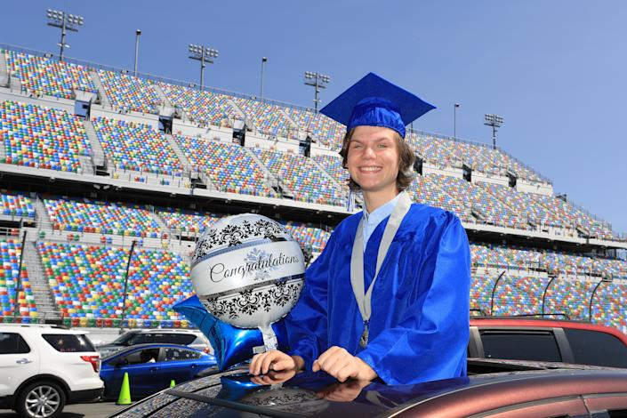 Graduates of Matanzas High School receive their diplomas on the track in their cars at Daytona International Speedway on May 31, 2020 in Daytona Beach, Florida. (PHOTO: Sam Greenwood/Getty Images)