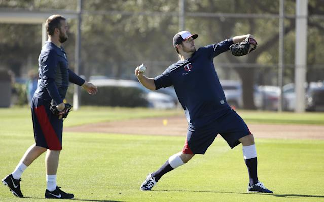 Minnesota Twins pitcher Phil Hughes, right, winds up for a throw as pitcher Glen Perkins, left, looks on during spring training baseball practice on Sunday, Feb. 16, 2014, in Fort Myers, Fla. (AP Photo/Steven Senne)