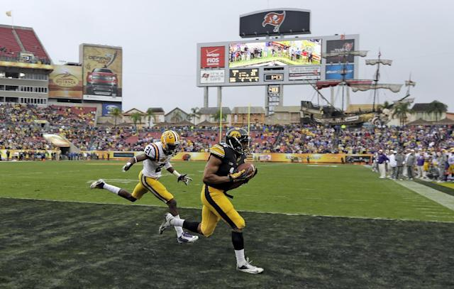 Iowa wide receiver Kevonte Martin-Manley (11) pulls in a 4-yard touchdown pass in front of LSU defensive back Rashard Robinson (21) during the fourth quarter of the Outback Bowl NCAA college football game Wednesday, Jan. 1, 2014, in Tampa, Fla. LSU won the game 21-14. (AP Photo/Chris O'Meara)