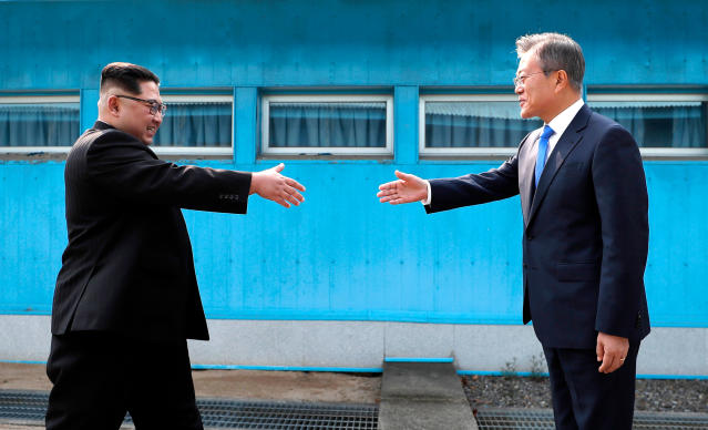 North Korean leader Kim Jong Un, left, prepares to shake hands with South Korean President Moon Jae-in over the military demarcation line at the border village of Panmunjom in Demilitarized Zone Friday, April 27, 2018. (Korea Summit Press Pool via AP)