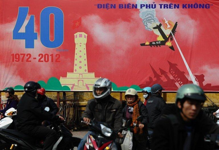 Motorcyclists pass a poster marking the 40th anniversary of the US Christmas bombing campaign, Hanoi, December 21, 2012